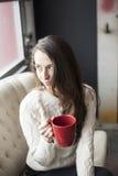 有布朗头发和眼睛的美丽的少妇喝咖啡的 免版税库存照片
