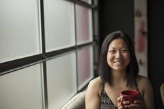 有布朗头发和眼睛的美丽的少妇用红色咖啡C 图库摄影