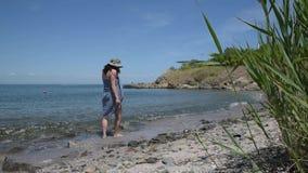 有布裙和帽子的白种人卷曲妇女走在海滩的 股票视频
