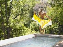 有布裙的妇女由游泳池 免版税库存照片