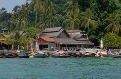 有帆船附载的大艇和木房子的热带村庄在棕榈树下 免版税库存照片