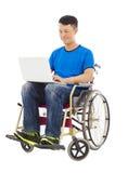 有希望的年轻人坐有膝上型计算机的一个轮椅 免版税库存照片