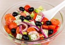 有希腊沙拉和塑料匙子的透明玻璃碗 库存图片