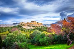 有帕台农神庙的上城 看法通过与绿色植物、树、古老大理石和都市风景,雅典的一个框架 免版税库存图片