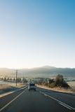 有带领往山的汽车的国家高速公路在日出 免版税库存照片
