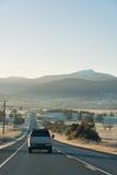 有带领往山的汽车的国家高速公路在日出 免版税库存图片
