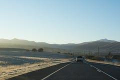 有带领往山的汽车的国家高速公路在日出 库存图片