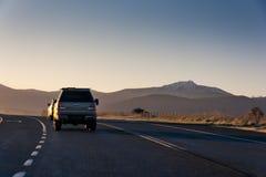 有带领往山的汽车的国家高速公路在日出 图库摄影