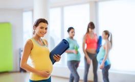 有席子的愉快的孕妇在健身房 免版税库存图片