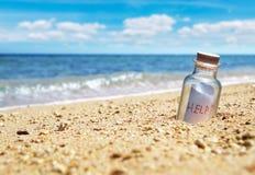 有帮助消息的瓶在海岸线 免版税库存照片