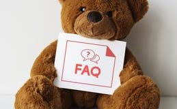 有常见问题解答卡片的熊玩偶 免版税库存图片