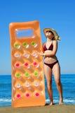 有帽子和可膨胀的床垫的白种人女孩在海滩 免版税库存图片