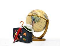 有帽子和地球的旅行手提箱 库存照片