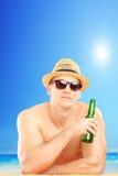 有帽子和太阳镜的微笑的人喝在beac的冰镇啤酒 免版税库存图片