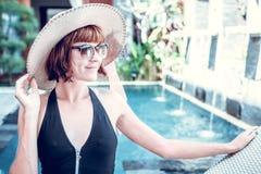 有帽子和太阳镜的秀丽性感的妇女享受她的暑假的在豪华别墅的游泳池 夏天 库存图片