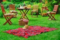有帽子和篮子的野餐毯子 党或野餐概念 免版税库存照片