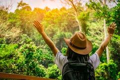 有帽子和背包身分的愉快的妇女游人和在年轻旅客享受美好的场面的热带森林里举她的手  图库摄影