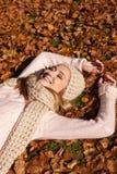 有帽子和围巾的年轻微笑的妇女室外在秋天 库存图片