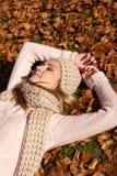有帽子和围巾的年轻微笑的妇女室外在秋天 免版税图库摄影