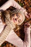 有帽子和围巾的年轻微笑的妇女室外在秋天 免版税库存图片