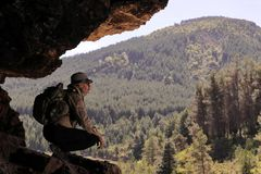 有帽子太阳镜和背包的探险家休息在洞的入口观看山的 免版税库存图片