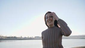 有帽子微笑的摆在的可爱的少女在湖附近的照相机 股票录像