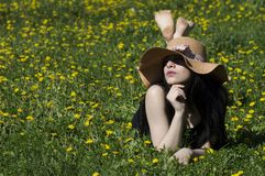 有帽子的女孩在蒲公英黄色花 免版税库存照片