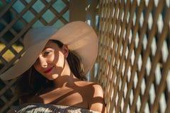有帽子的女孩微笑在树荫下的 免版税库存图片