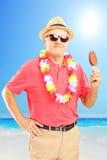有帽子的微笑的绅士吃在海滩的巧克力冰淇凌 库存图片