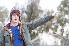 有帽子的指向他的手指的一个年轻人的画象 免版税图库摄影