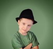 有帽子的时尚男孩在绿色背景 免版税库存图片