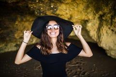 有帽子的晒日光浴在岩石的美丽的墨西哥妇女和太阳镜在夏天职业时间靠岸 库存图片