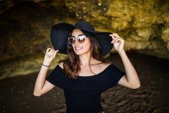 有帽子的晒日光浴在岩石的美丽的拉丁妇女和太阳镜在夏天职业时间靠岸 库存图片