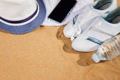 有帽子的白色运动鞋在沙子 库存图片