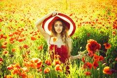 有帽子的美丽的女孩在红色鸦片领域 免版税库存图片