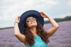 有帽子的美丽的女孩,微笑在淡紫色领域 免版税库存照片