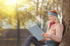 有帽子的年轻女性读书和享用在同水准的太阳 库存照片