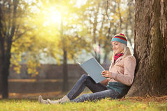 有帽子的年轻女性读书和享用在同水准的太阳 免版税库存图片