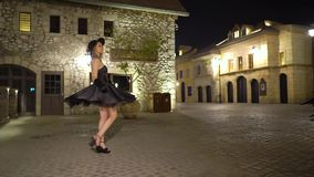 有帽子调情的人的,单独步行愉快的少妇在古城在晚上 黑减速火箭的蓬松礼服的快乐的性感的女孩 股票录像