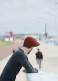 有帽子转动的头的年轻人 库存照片