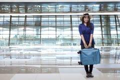 有帽子运载的行李的微笑的亚裔妇女旅行家 免版税库存照片
