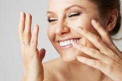 有干净的皮肤、自然构成和白色牙的美丽的微笑的妇女在灰色背景 接近的纵向 医疗 免版税库存照片