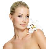 有干净的皮肤和白花的美丽的妇女 免版税库存照片
