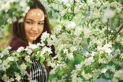 有干净的皮肤的少妇在一棵开花的苹果树附近 女孩柔和的画象在春天公园 免版税库存照片