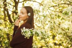 有干净的皮肤的少妇在一棵开花的苹果树附近 女孩画象在春天公园 免版税库存图片
