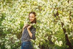 有干净的皮肤的少妇在一棵开花的苹果树附近 女孩画象在春天公园 库存图片