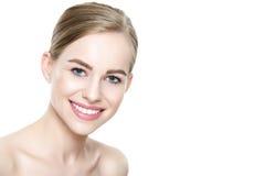 有干净的皮肤的美丽的年轻白肤金发的微笑的妇女,自然构成和完善白色牙 免版税图库摄影
