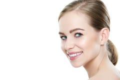 有干净的皮肤的美丽的年轻白肤金发的微笑的妇女,自然构成和完善白色牙 免版税库存照片