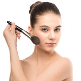 有干净的面孔的年轻深色的妇女 应用化妆刷子的女孩完善的皮肤 笤帚查出的白色 图库摄影