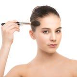 有干净的面孔的年轻深色的妇女 应用化妆刷子的女孩完善的皮肤 笤帚查出的白色 库存图片